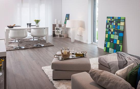 Modernes, weißes Wohnzimmer mit Laminatboden und Mobiliar in Hellgrau