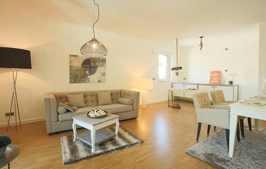 Offenes Wohnzimmer mit einem Laminatboden, sowie grauem und weißem Mobiliar