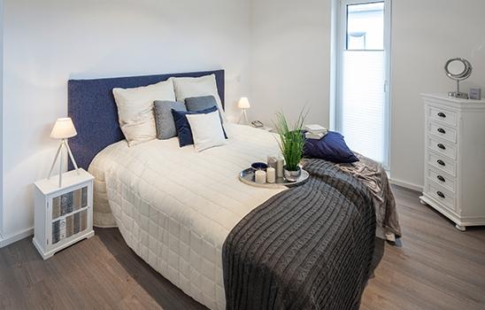 Doppelbett mit weißen Laken und einer blauen Rückwand
