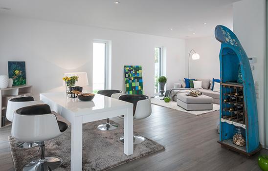 Helles, modernes Wohnzimmer mit grau-braunem Laminatboden und einem Weinregal aus einem aufrecht stehenden Schiffsbug