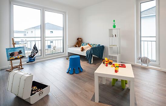 Weißes Kinderzimmer mit viel Tageslicht und einem sauberen Laminatboden