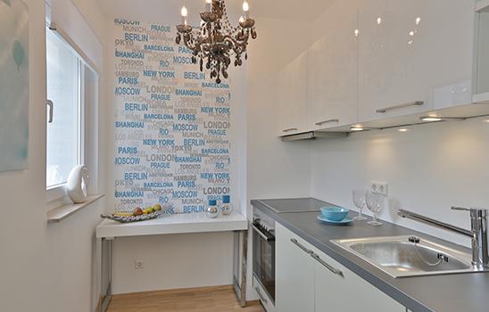 Weiße Küche mit einem schicken Kronleuchter und einem Wandtattoo mit vielen Städtenamen