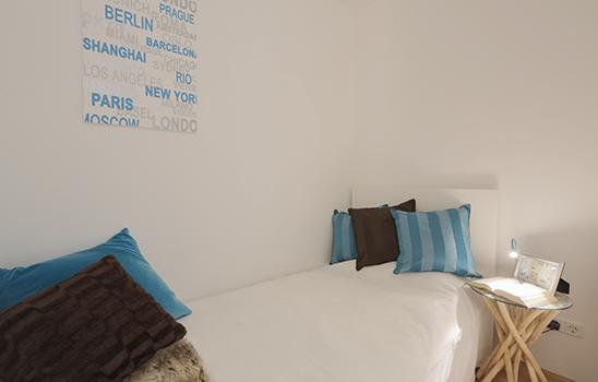 Weißes Bett mit blauen und dunkelbraunen Kissen