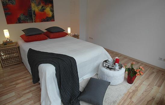 Weißes Doppelbett mit roten und grauen Akzenten