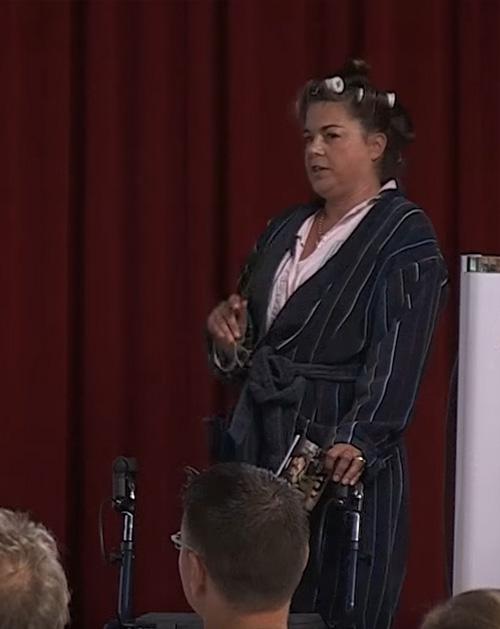 Gerda Müller im Bademantel mit Lockenwicklern bei einem Vortrag