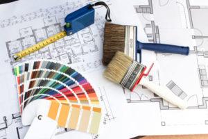 Farbfächer, Pinsel und Bandmaß liegen auf einer technischen Zeichnung
