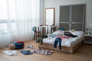 Kleidungsstücke auf einem Bett und auf dem Boden